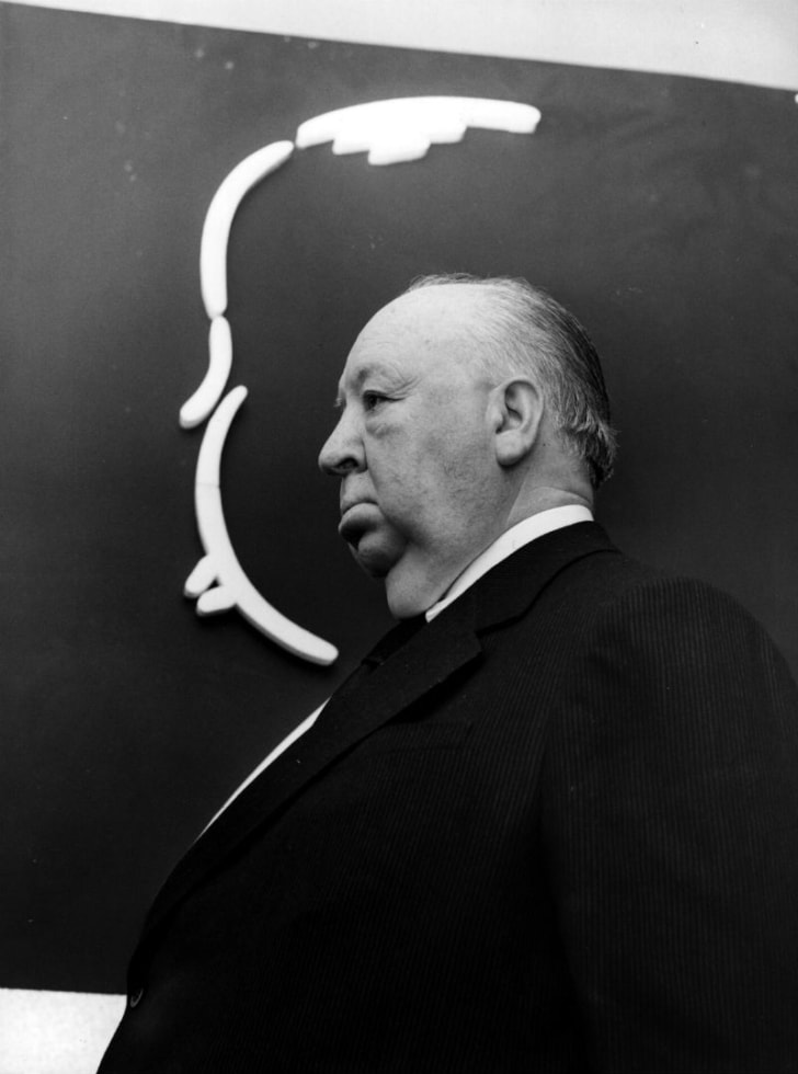 Director Alfred Hitchcock stands in front of a drawing of his silhouette