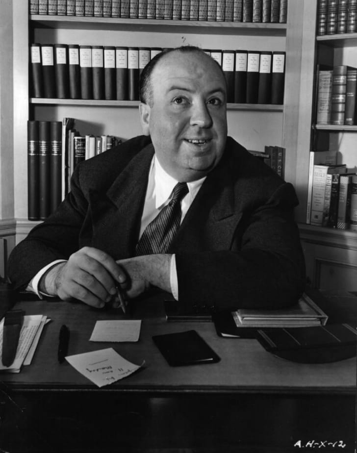 Director Alfred Hitchcock is photographed sitting behind a desk