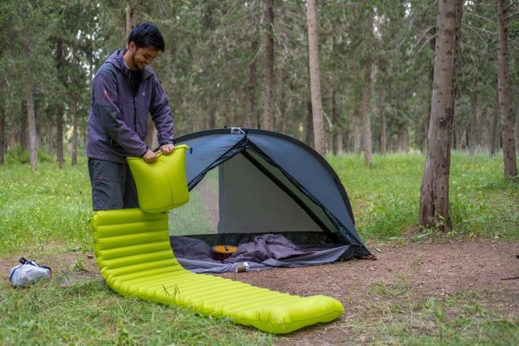 A man setting up his air mattress near his RhinoWolf tent