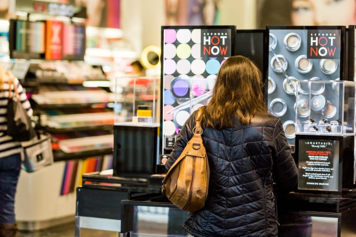 A woman stands in front of a makeup display in Sephora