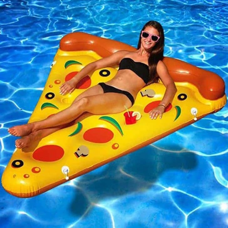 Woman lounging on pizza slice.