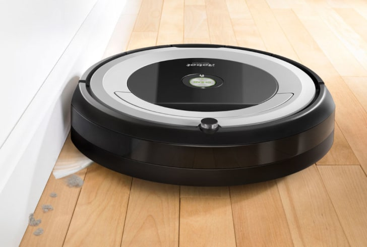 A Roomba 690 picks up dust along a wall.