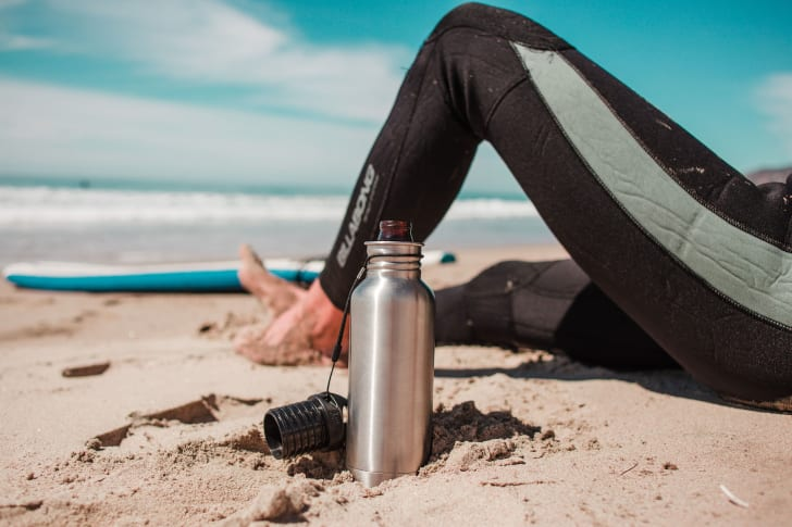 An open beer inside a BottleKeeper stands in the sand next to a surfer in a wetsuit.