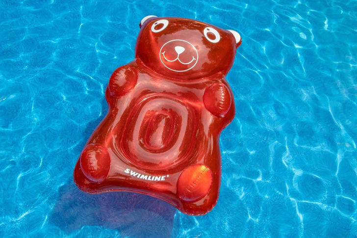 A pool float shaped like a red gummy bear
