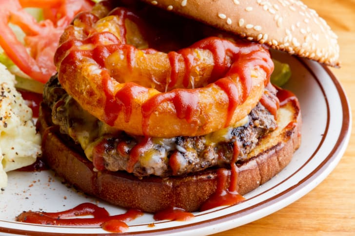 hamburger with onion rings and barbeque sauce