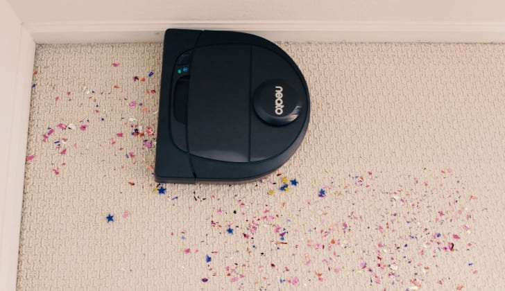 A Neato Botvac D6 Connected vacuum picks up confetti on a carpeted floor.