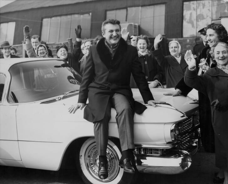 Liberace sitting on the hood of a 1960s car