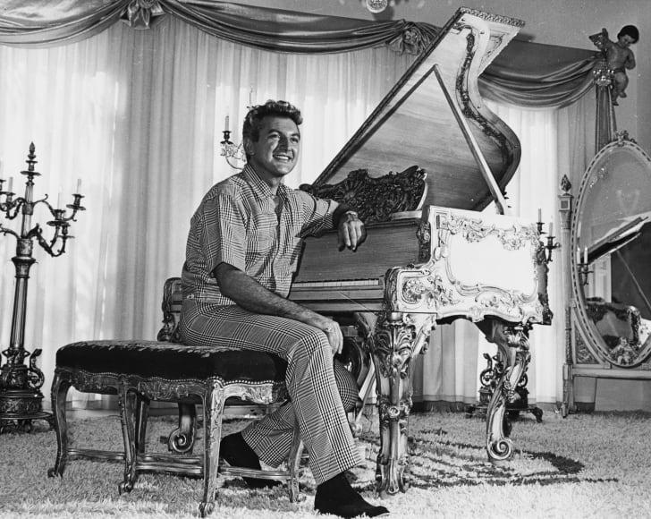 Liberace sits at a grand piano