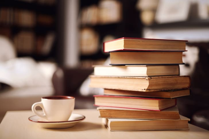 A stack of books on a table next to a cup and saucer