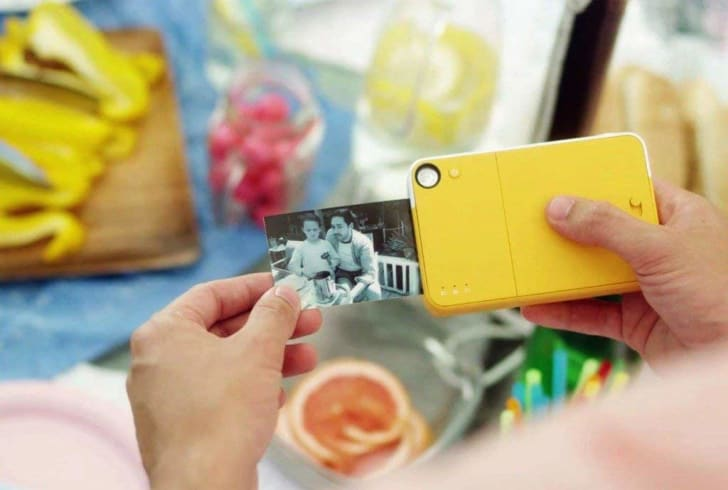 A person prints out a black-and-white photo from a yellow PRINTOMATIC camera.