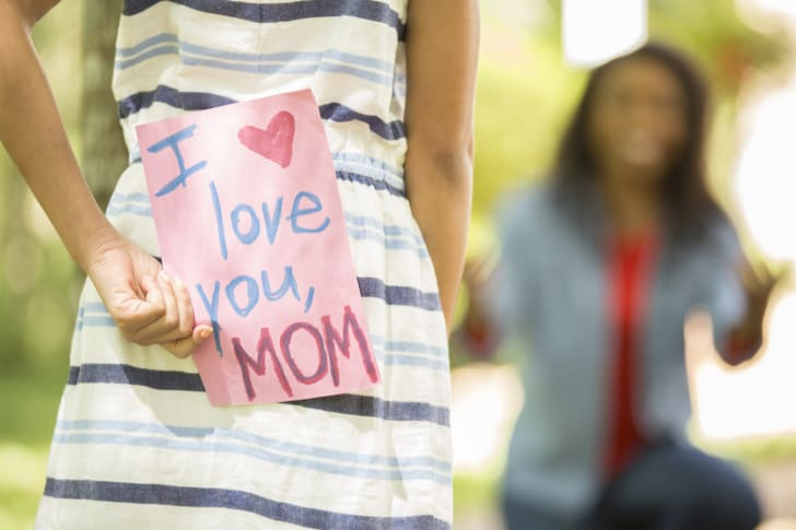 A young girl gives her mom a handmade Mother's Day card