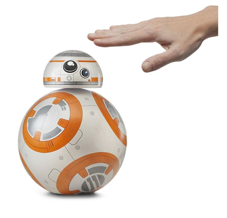 A hand reaches out to tap the top of a BB-8-shaped lamp