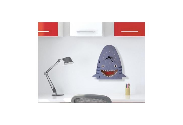 A clock shaped like a shark hangs on the wall above a desk