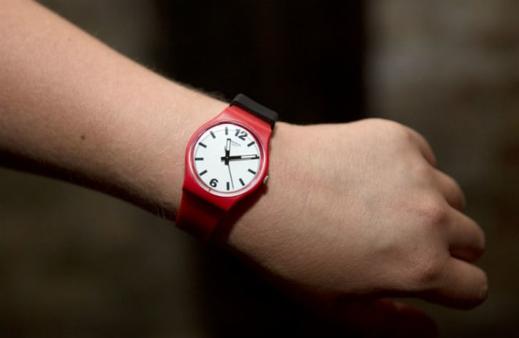 A person models a Swatch watch on their wrist