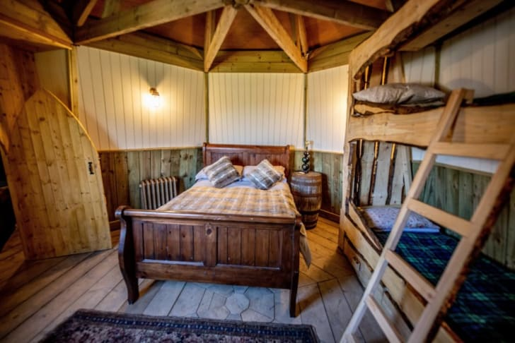 Interior of Hagrid's hut cottage shows a bed and bunk beds.