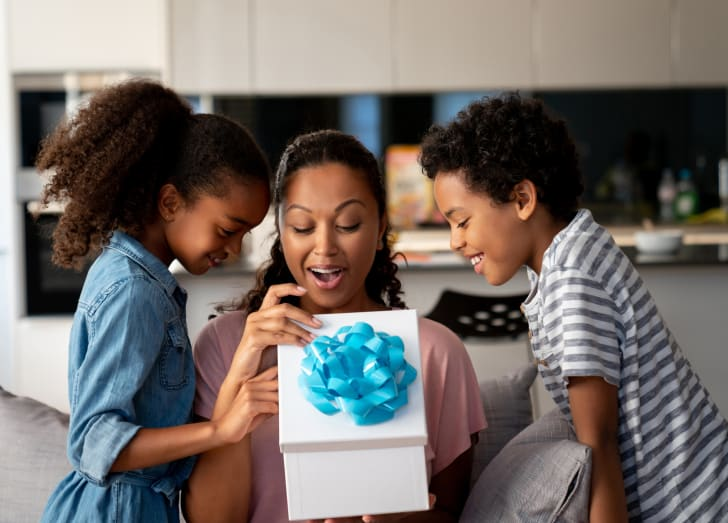 Happy kids surprising their mother with a gift for Mother's Day