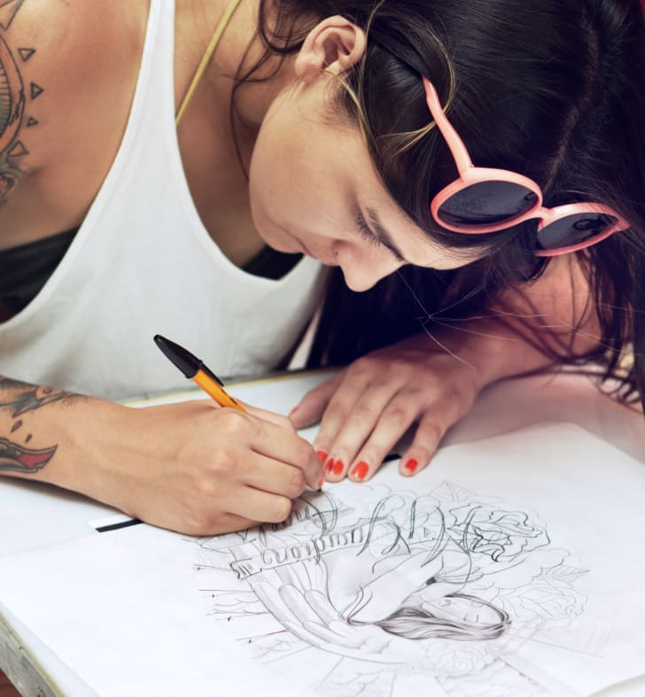 A female tattooist bent over a drawing