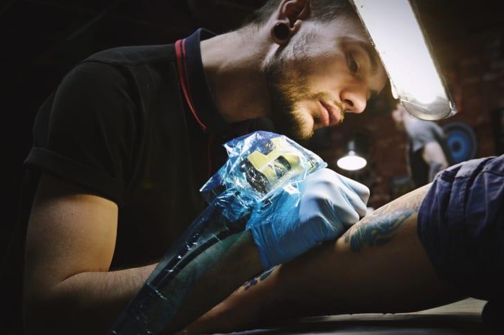 A male tattooist at work