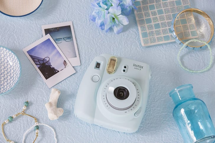 A Fujifilm instant camera on a table with several printed photos