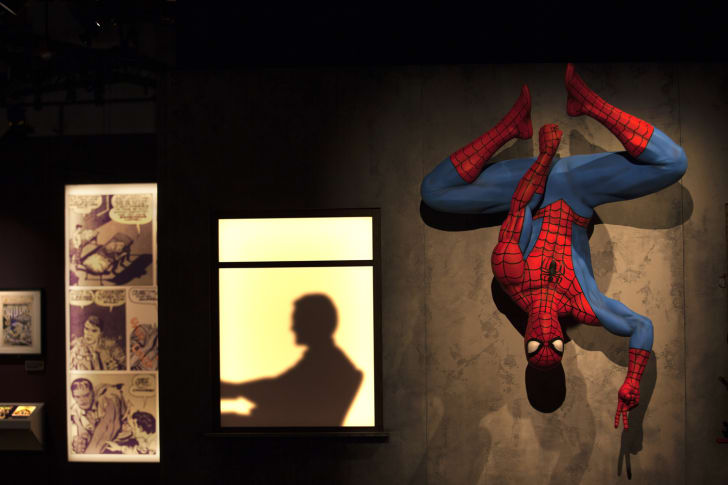 Spiderman hangs from a wall