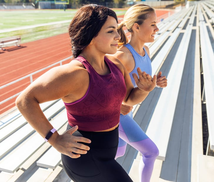 Two women run up the bleachers at a stadium with Fitbits on.