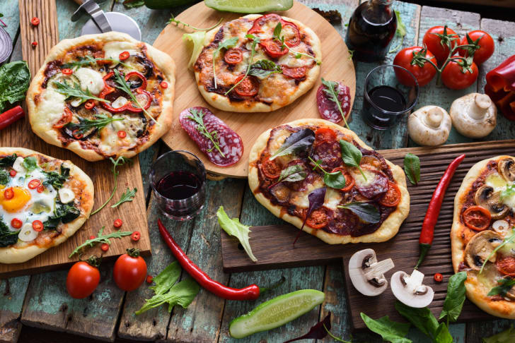A table full of freshly made pizzas