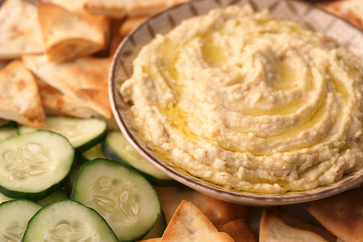 A fresh bowl of hummus with cucumbers