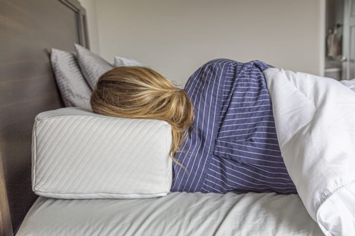 woman in bed with head resting on pillow cube