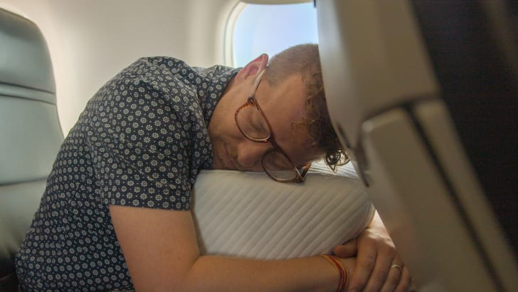 guy sleeping on pillow cube in air plane
