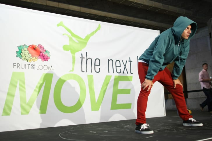 """A man in red pants stands on stage in front of a sign that says """"the next move"""" with the Fruit of the Loom logo—which consists of various fruits—on it."""