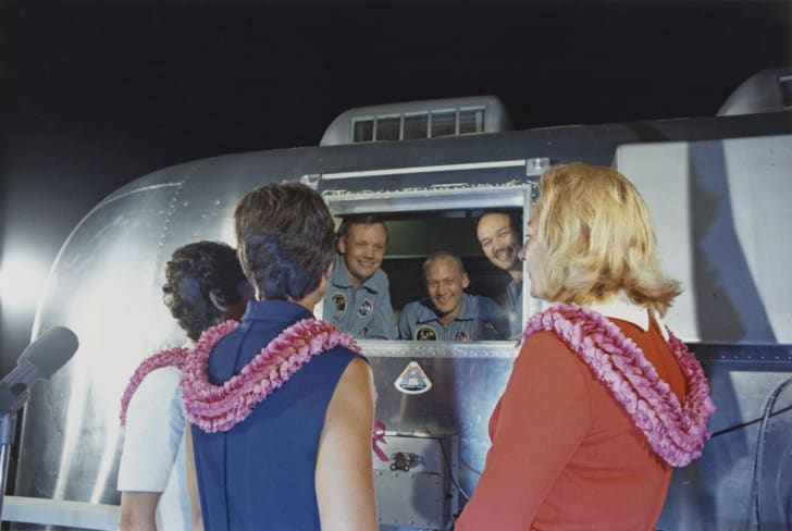 The three crew members of NASA's Apollo 11 lunar landing mission are greeted by their wives after their arrival at Ellington Air Force Base near Houston in Texas in a Mobile Quarantine Facility (MQF) earlier that day, 27th July 1969