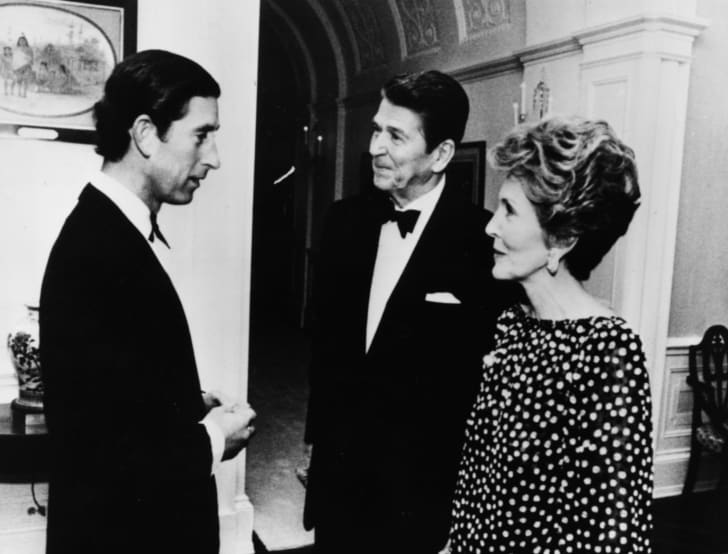 Prince Charles talking to President Ronald Reagan and his wife Nancy at a private dinner in the White House in 1981.