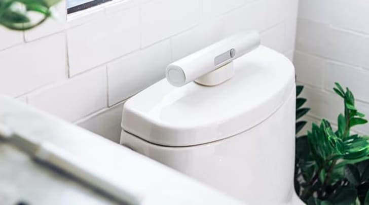 Portable bidet charging on toilet.