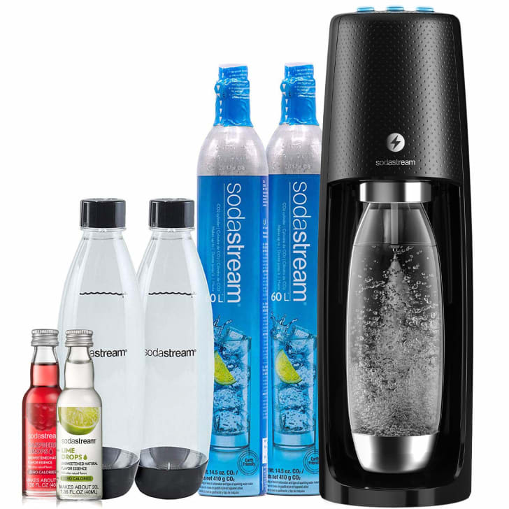 An SodaStream Fizzi with two extra bottles, two carbon dioxide cylinders, and two flavor bottles.
