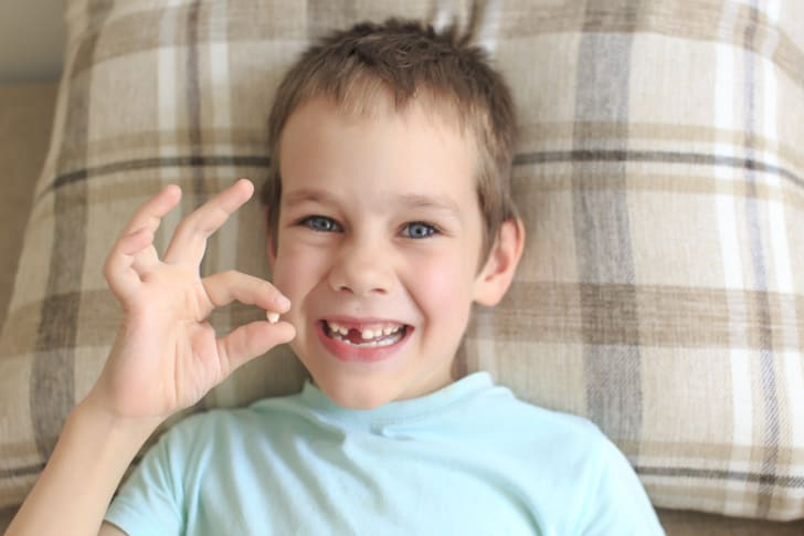 Young boy who has lost a tooth gets ready to put it under his pillow for the Tooth Fairy