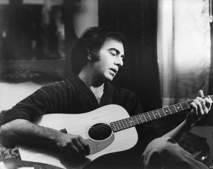 American pop singer-songwriter Neil Diamond relaxes with his guitar. Diamond is shortly to make his film debut in a remake of 'The Jazz Singer'