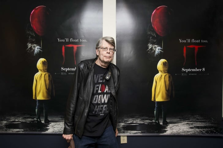 Stephen King in front of poster for IT.