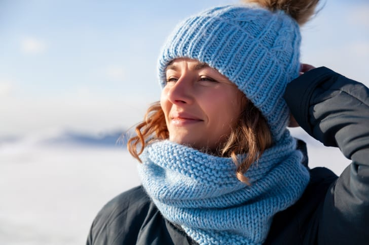 A woman in a light blue knit cap and blue knit scarf enjoys the sun on her face in the snow