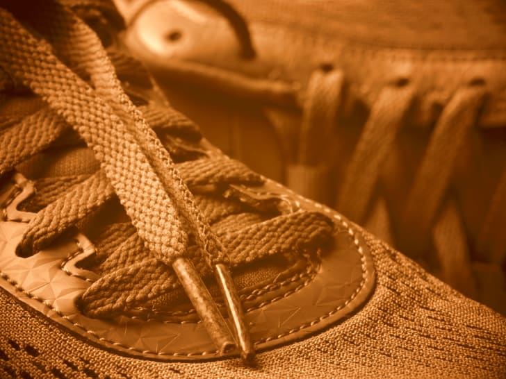 Close up of gold shoes with laces