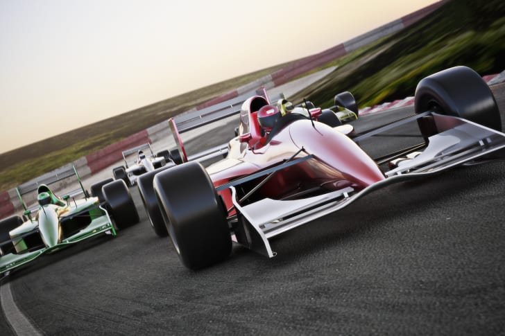 A red formula one racecar at the front of a pack of racecars