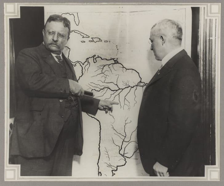Theodore Roosevelt poses with a map of the roosevelt-rondon expedition