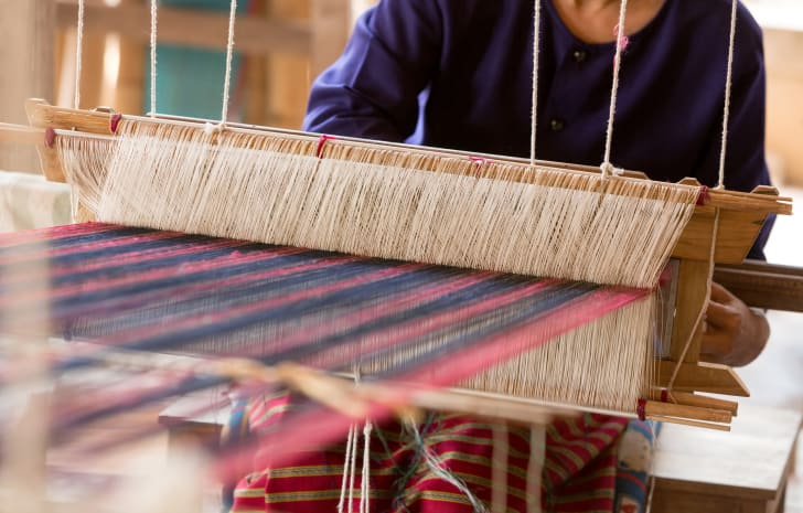 A woman weaving at a hand loom.