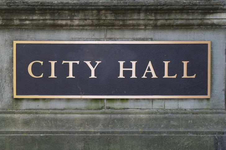 A black sign with golden letters reading City Hall