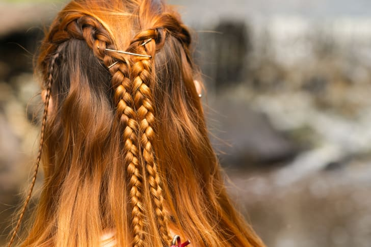 An intricate braid in the hair of a redheaded woman.
