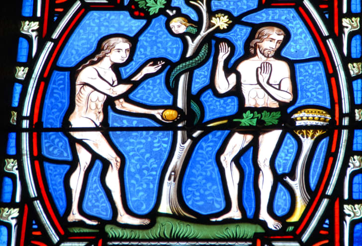 Stained glass depiction of Adam and Eve in the garden with a snake.
