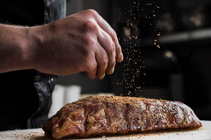 A male chef's hand seasons a rack of ribs.
