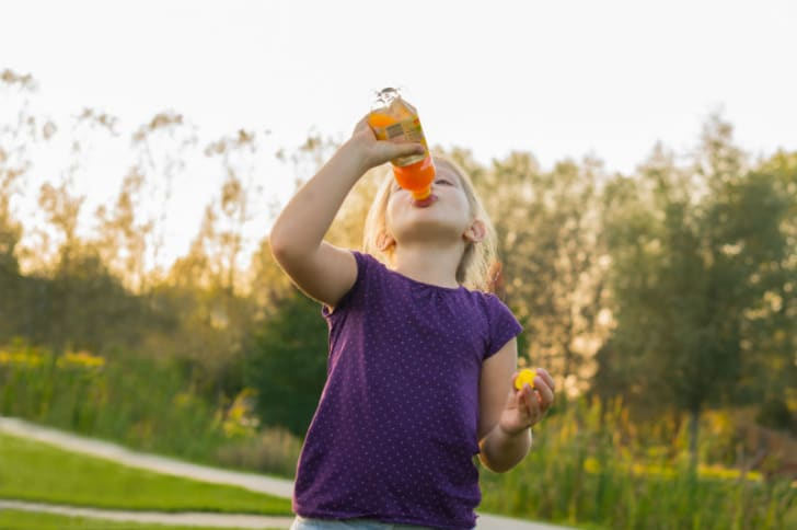 A child drinking from a juice bottle is pictured