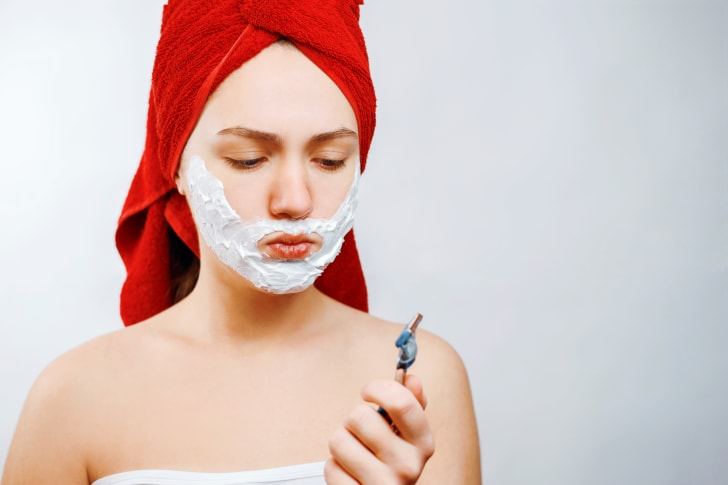 A young woman contemplates shaving her face with a razor.