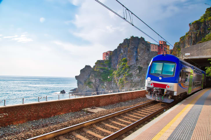 A modern train travels out of a cliffside tunnel in Italy