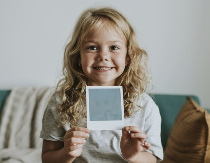 Little girl holds up a photo taken with an instant camera